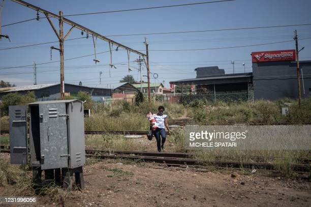 Woman crosses the railway near the Wonderboom train station in Pretoria, on March 10, 2021. - South Africa's metro rail infrastructure has been...