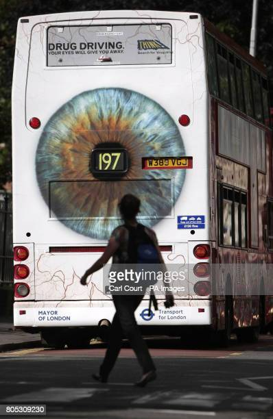 A woman crosses the road behind a bus displaying Transport for London's new Drug Driving campaign poster in Croydon London