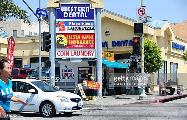 A woman crosses the road in front of a strip mall near the intersection of Normandie and Beverly in Los Angeles on April 27 2012 in California ahead...
