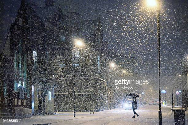 A woman crosses the road in heavy snow on December 21 2009 in London United Kingdom Snow and freezing temperatures have brought travel disruption to...