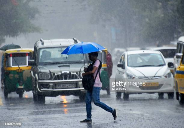 A woman crosses the road in Kolkata on 03 May 2019 as the cyclonic storm Fani hits the coastal places of Orissa and West Bengal on 03 May 2019 Due to...