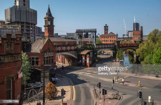 Woman crosses the road outside Atlas Bar on Deansgate in central Manchester on April 25, 2020 in Manchester, United Kingdom. The British government...