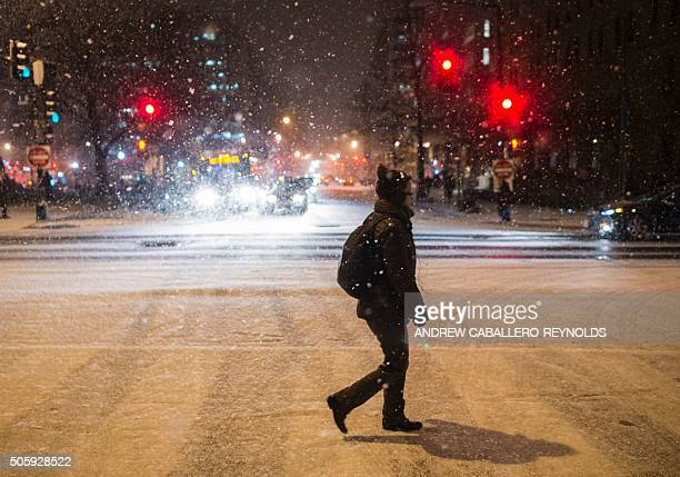 A woman crosses the street as it snows in Washington DC on January 20 2016 / AFP / Andrew CaballeroReynolds