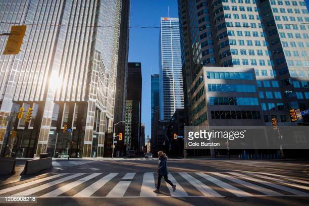 Woman crosses the street during morning commuting hours in the Financial District as Toronto copes with a shutdown due to the Coronavirus, on April...