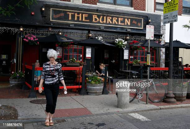 A woman crosses the street in front of The Burren in Davis Square in Somerville MA on May 29 2018