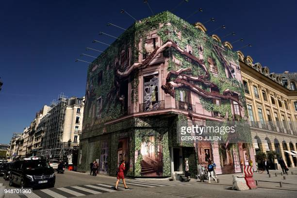 A woman crosses the street near a giant advertising tarpaulin on the facade of French jewellery Boucheron on the Place Vendome on April 19 in Paris