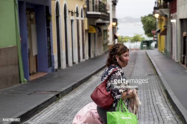 A woman crosses the street with her dog as residents prepare for a direct hit from Hurricane Maria on September 19 2017 in San Juan Puerto Rico...