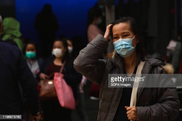 A woman crosses the streets of Central during a weekend wearing surgical face masks following the outbreak of the Wuhan Corona virus As of early...