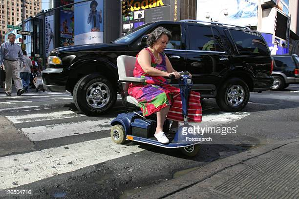 Woman crossing a busy city street using a scooter.
