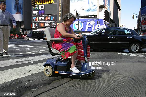 Woman crossing a city street using a scooter/cart.