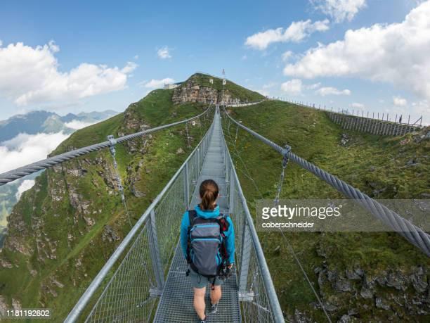 woman crossing a suspension bridge, austrian alps, bad gastein, salzburg, austria - hängebrücke stock-fotos und bilder