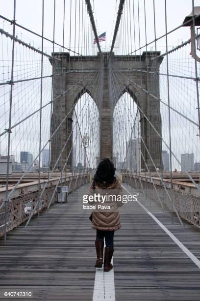 Woman crossing Brooklyn bridge, New York