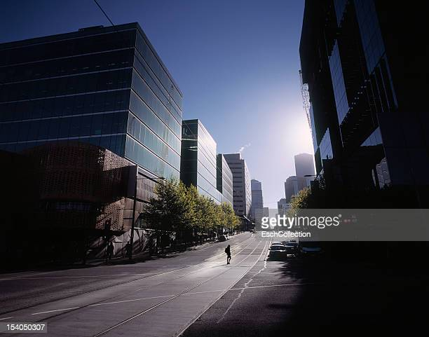 woman crossing empty street in melbourne at dawn - sparse stock pictures, royalty-free photos & images