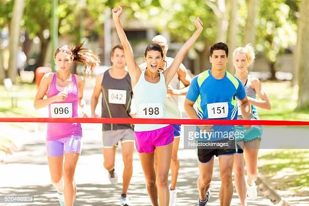 Mujer cruzando Finish Line de maratón en el parque