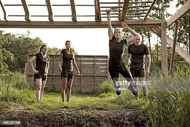 woman crossing monkey bars during obstacle run - barracks stock pictures, royalty-free photos & images