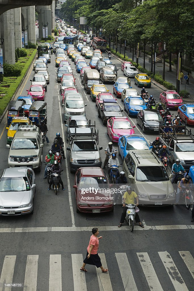 Woman crossing Ratchadamri Road in front of congested traffic. : ストックフォト