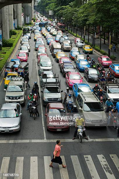 woman crossing ratchadamri road in front of congested traffic. - ラチャダムリ通り ストックフォトと画像