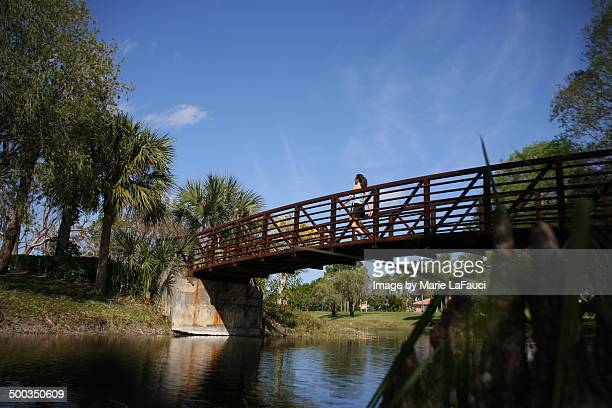 woman crossing red bridge - marie lafauci stock pictures, royalty-free photos & images
