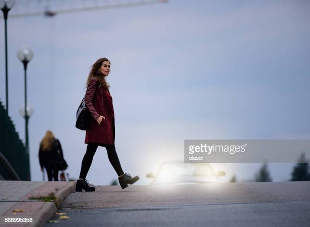 woman crossing road dark bridge, car in background - pedestrian crossing stock photos and pictures