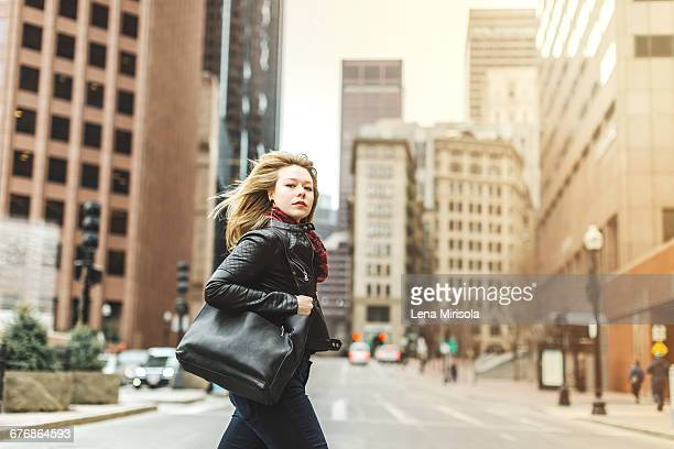 woman crossing road in urban area, boston, massachusetts, usa - leather purse stock pictures, royalty-free photos & images