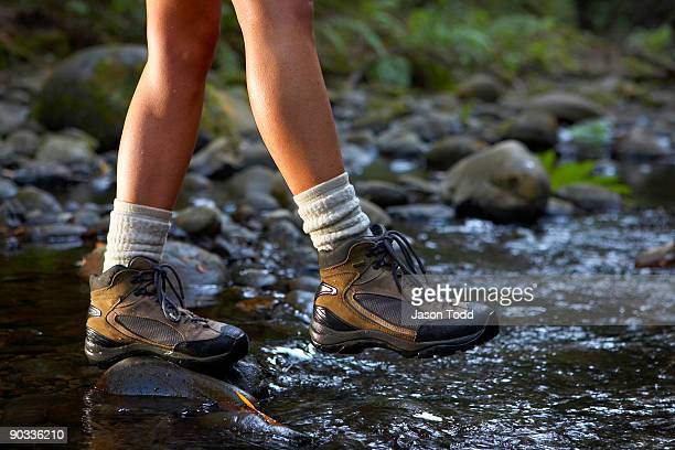woman crossing stream wearing hiking boots - jason todd stock photos and pictures