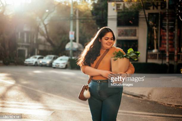 woman crossing street - three quarter length stock pictures, royalty-free photos & images