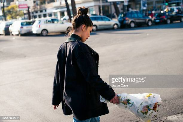 woman crossing street with a bunch of flowers in her hand - topknot stock pictures, royalty-free photos & images