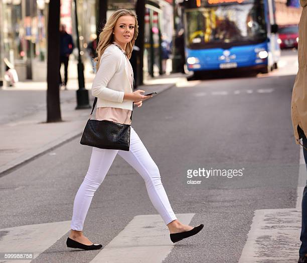 Woman crossing street, zebra crossing, bus and traffic in background