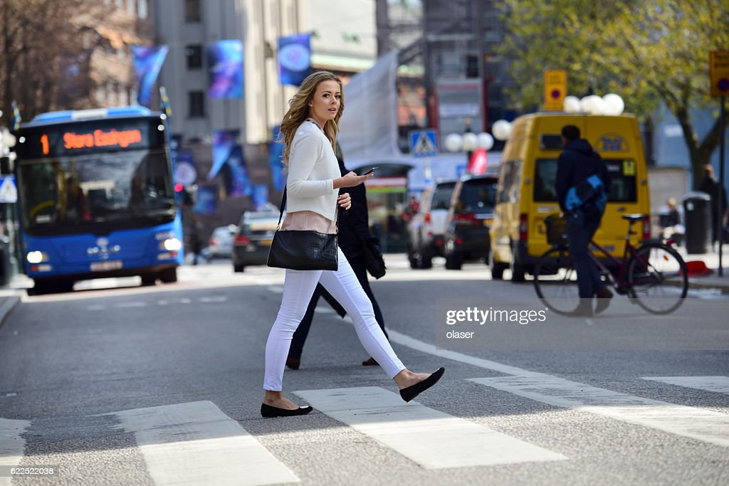 Woman crossing street, zebra crossing, bus and traffic in background : Stock Photo