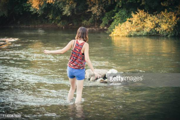 woman crossing the river - wading stock pictures, royalty-free photos & images