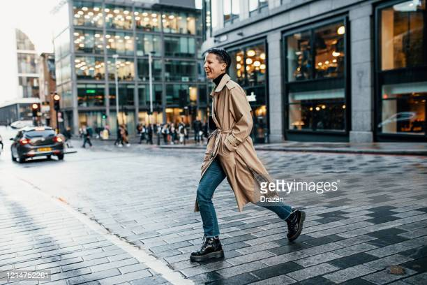 woman crossing the street in abandoned downtown due to lock down - crossing stock pictures, royalty-free photos & images