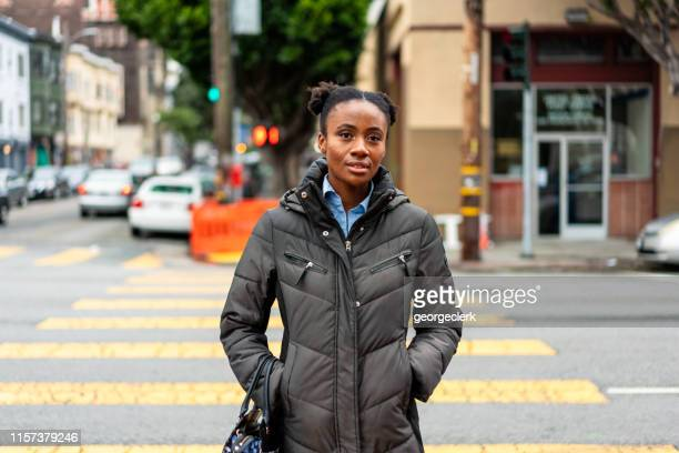 woman crossing the street in san francisco, california - winter coat stock pictures, royalty-free photos & images