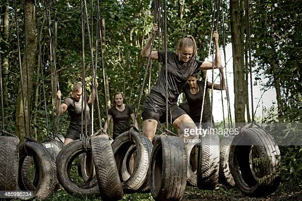 woman crossing tyre obstacle during outdoors mud run