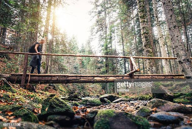 Woman Crossing Wooden Bridge In The Forest