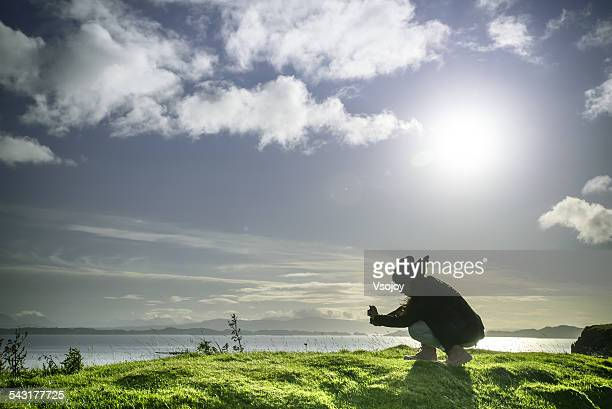 woman crouched down shooting beautiful landscape - vsojoy stock pictures, royalty-free photos & images