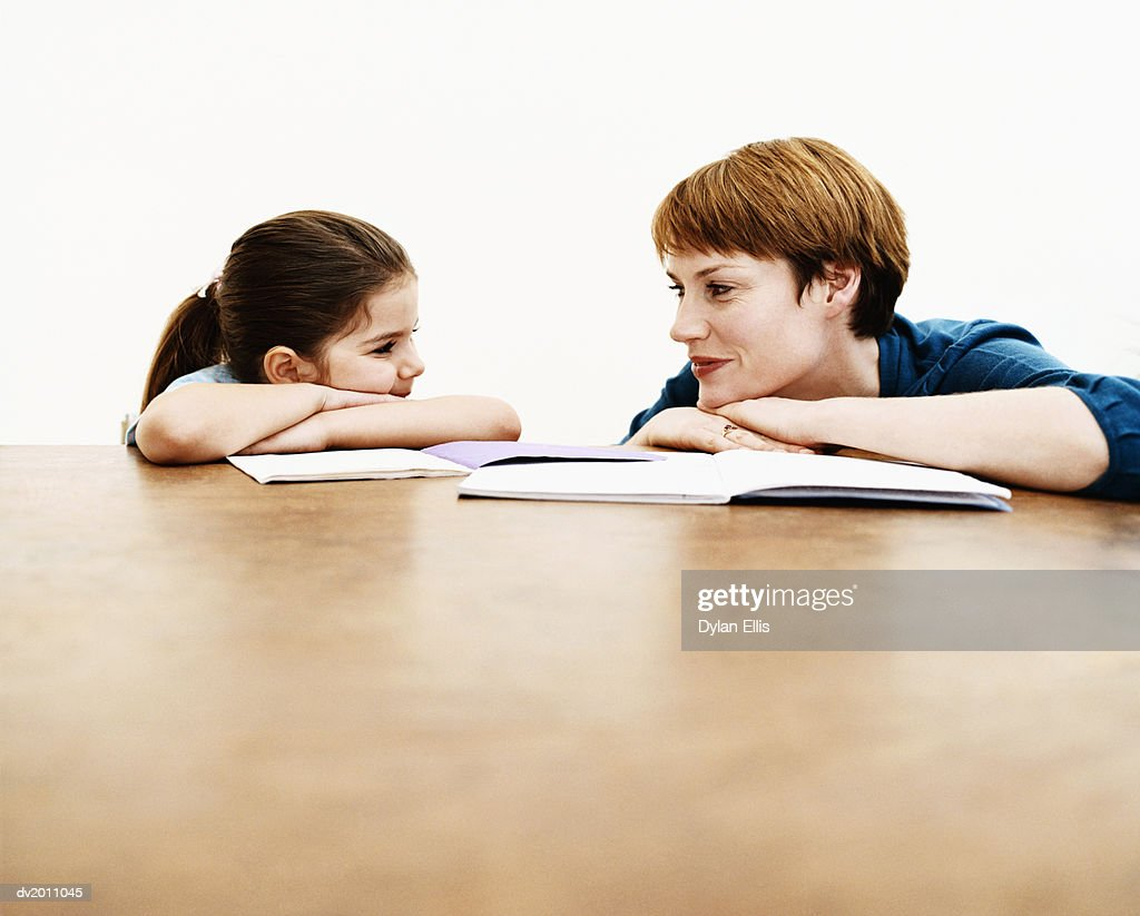 Woman Crouches at a Table With Her Young Daughter, Teaching Her From Books : Stock Photo
