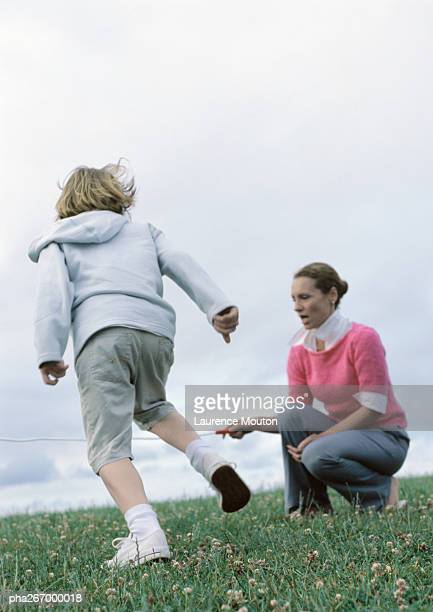 Woman crouching holding end of jump rope for boy preparing to jump