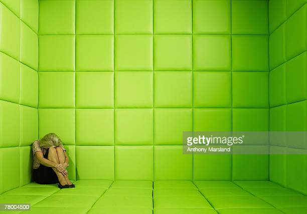 Woman crouching in corner of green padded cell