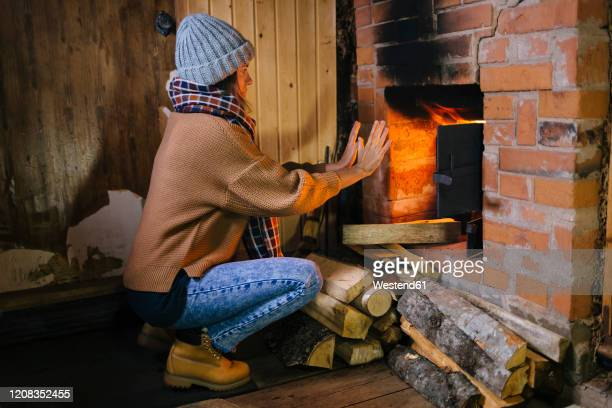 woman crouching in front of fireplace warming her hands - warming up stock pictures, royalty-free photos & images