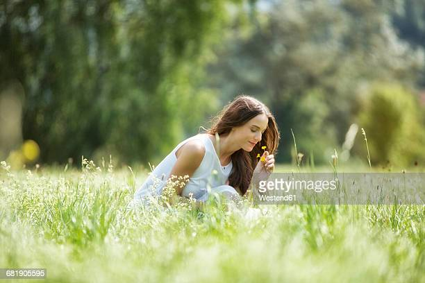 Woman crouching on a meadow smelling flowers