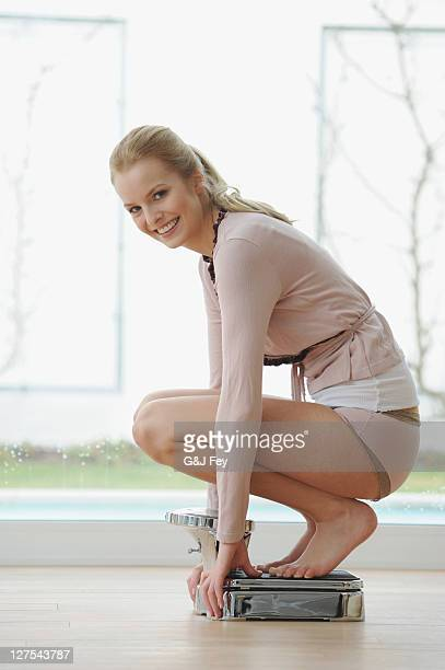 Woman crouching on bathroom scale