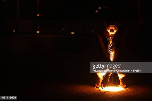 Woman Crouching On Lit Recessed Light At Night
