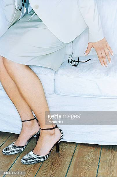 Woman crouching to sit, glasses on sofa, close-up