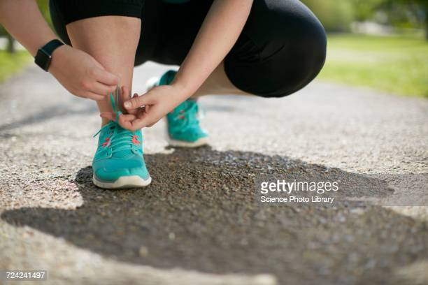 Woman crouching, tying up trainers
