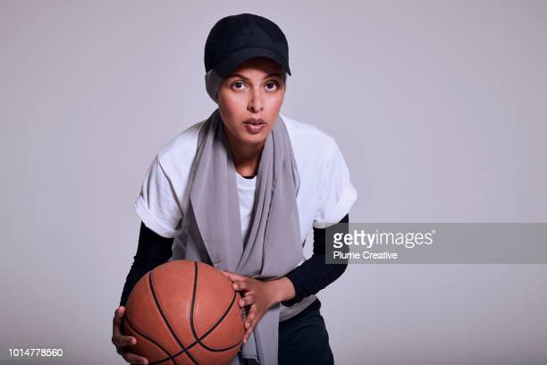 Woman crouching with basketball