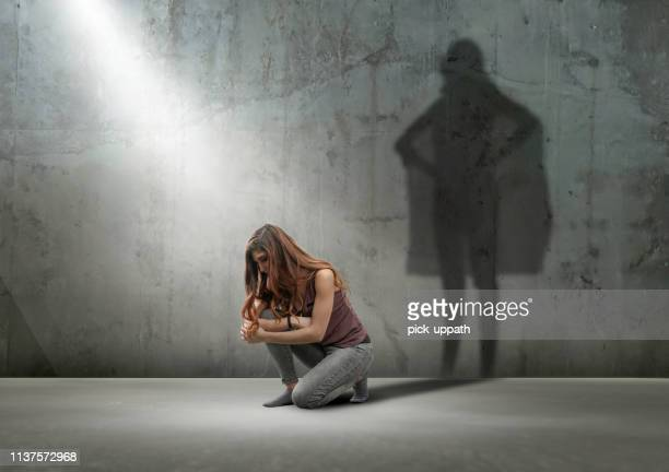 woman crouching with shadow as super hero - heroes stock pictures, royalty-free photos & images