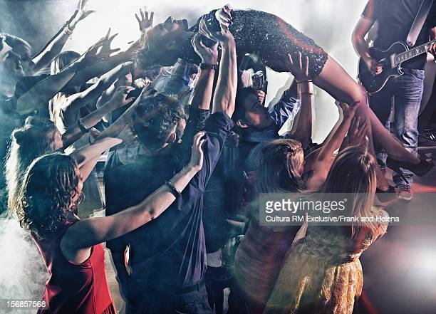 Woman crowdsurfing in club