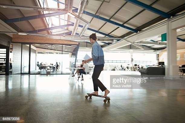 Woman cruising on longboard at creative office