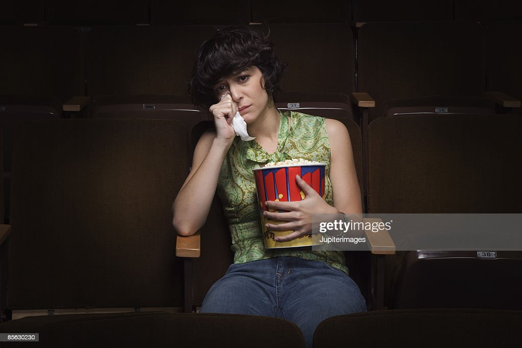 Woman crying in movie theatre : Stock Photo