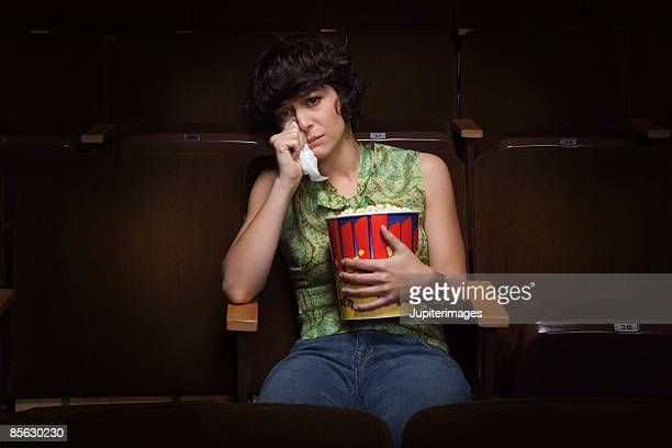 Woman crying in movie theatre